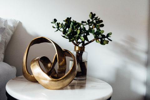 "A brass and metal sculpture on a marble table describing ""Luxe"" trend in home decor"