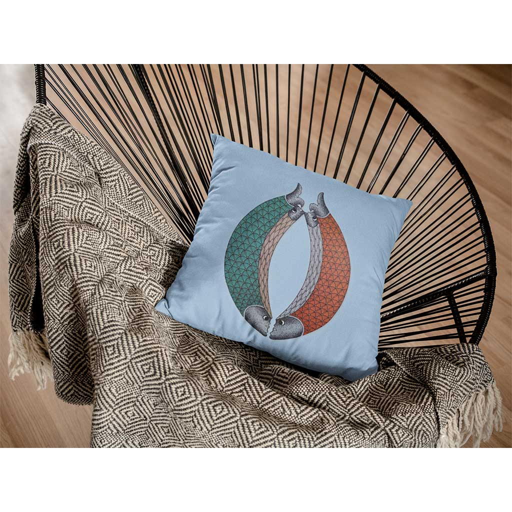 Blue cushion with two fishes with green and red scales on a chair with a blanket