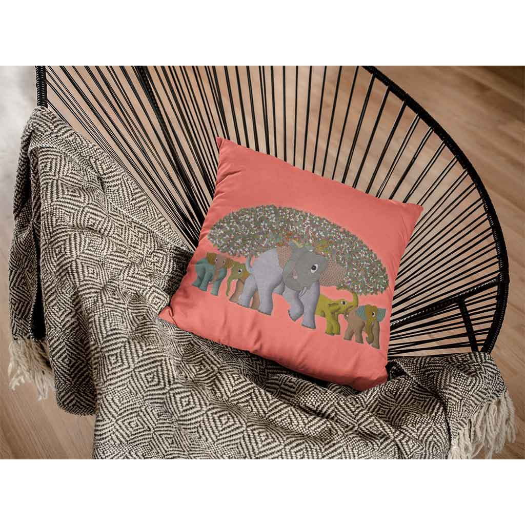 Coral cushion cover with an image of herd of elephants and tree set on a chair with a blanket