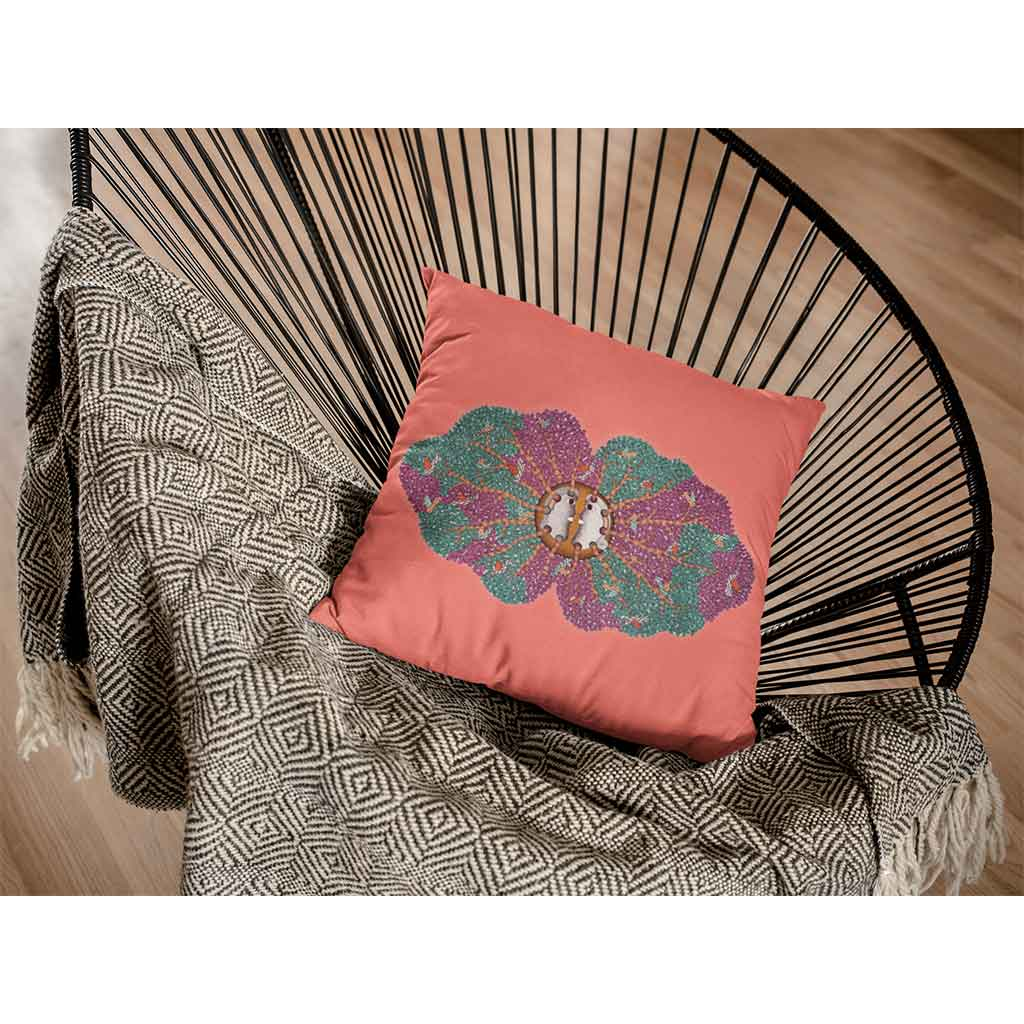 Coral cushion with purple and green tree motif on a chair