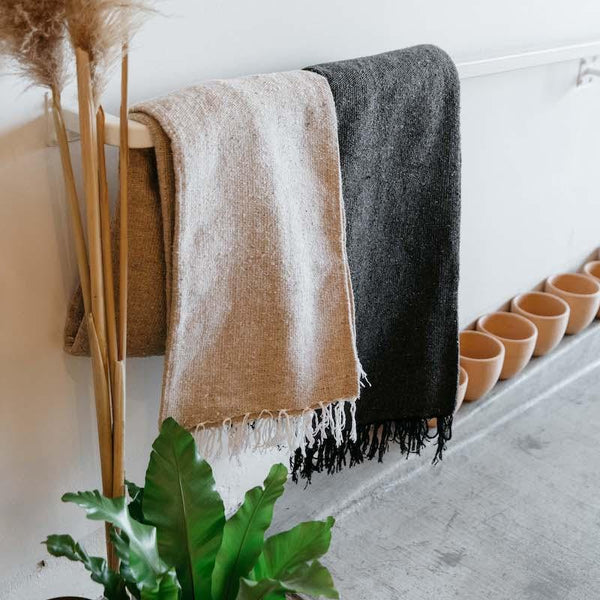 PF Candle Co charcoal and tan blankets hanging up over pots and a plant