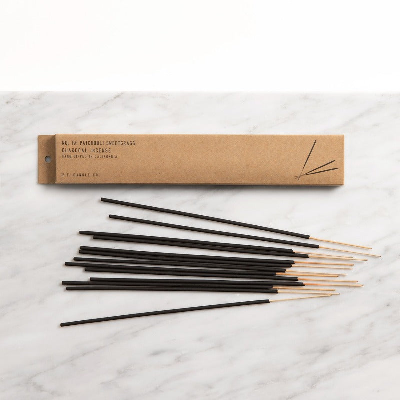 PF Candle Co Classic Line Patchouli Sweetgrass incense sticks on a marble counter with the kraft packaging box