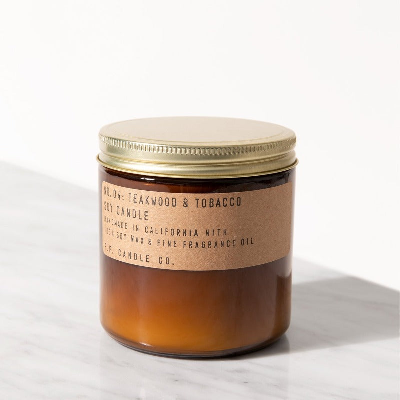 PF Candle Co Teakwood and Tobacco amber jar large candle with kraft label and brass lid on a marble counter