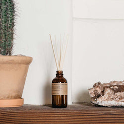 Patchouli Sweetgrass amber glass reed diffuser on a wood shelf between a potted cactus and crystal