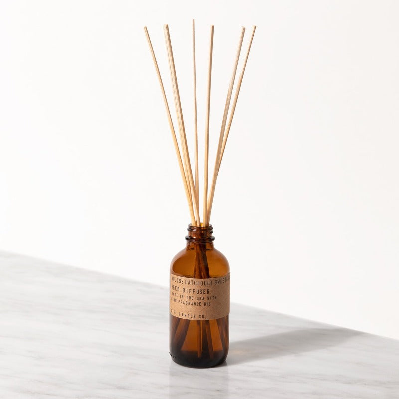 PF Candle Co Patchouli Sweetgrass classic line reed diffuser in a glass bottle with kraft label with rattan reed sticks inside