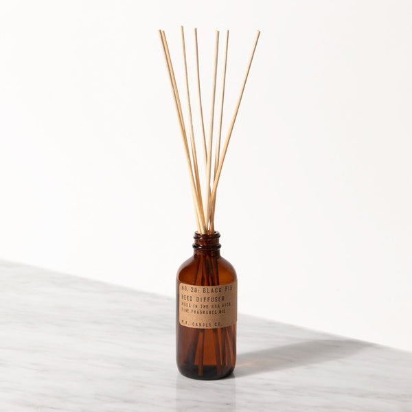 PF Candle Co Black Fig classic line reed diffuser in a glass bottle with kraft label with rattan reed sticks inside