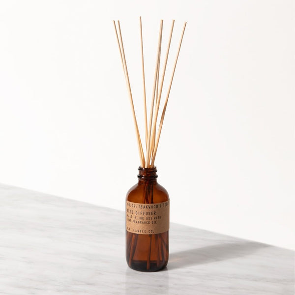 PF Candle Co Teakwood and Tobacco classic line reed diffuser in a glass bottle with kraft label with rattan reed sticks inside
