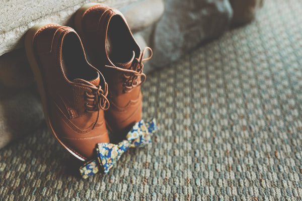 Grooms camel-colored dress shoes and floral printed bowtie.