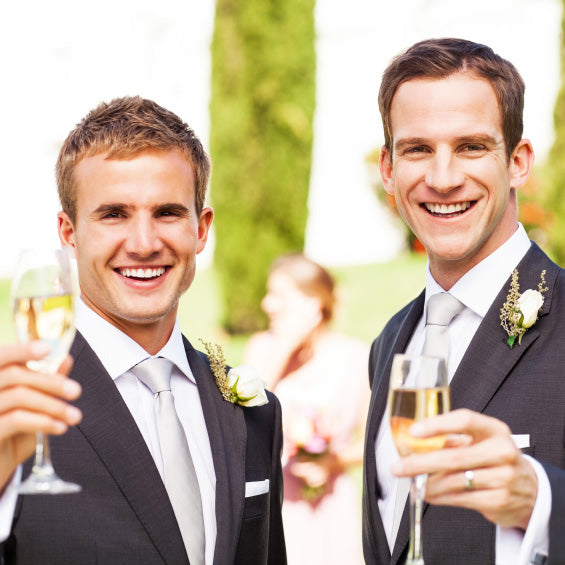 Groom And Best Man Toasting Champagne Flutes At Garden Wedding