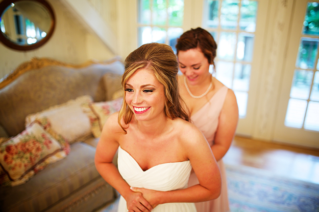 Bridesmaid Buttoning Up Brides Gown