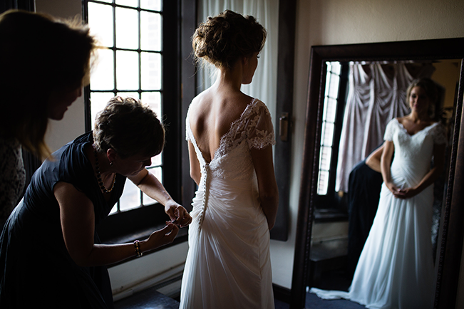 bride-getting-buttoned-up