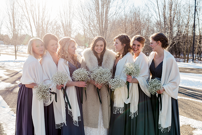 bride wearing a warm jacket and the bridesmaids wear scarves for a cold winter wedding