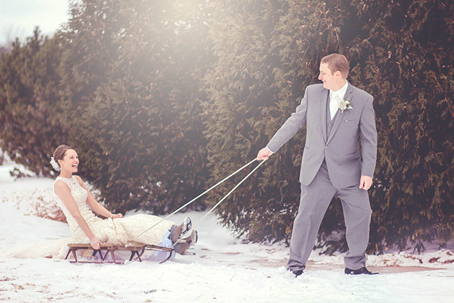 groom pulling bride on a sled