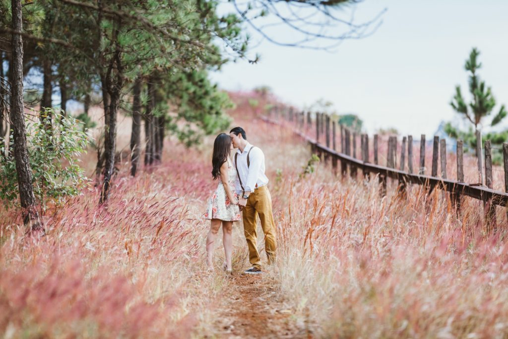 couple kissing in field | How to Pick the Perfect Fall Engagement Photos Outfit