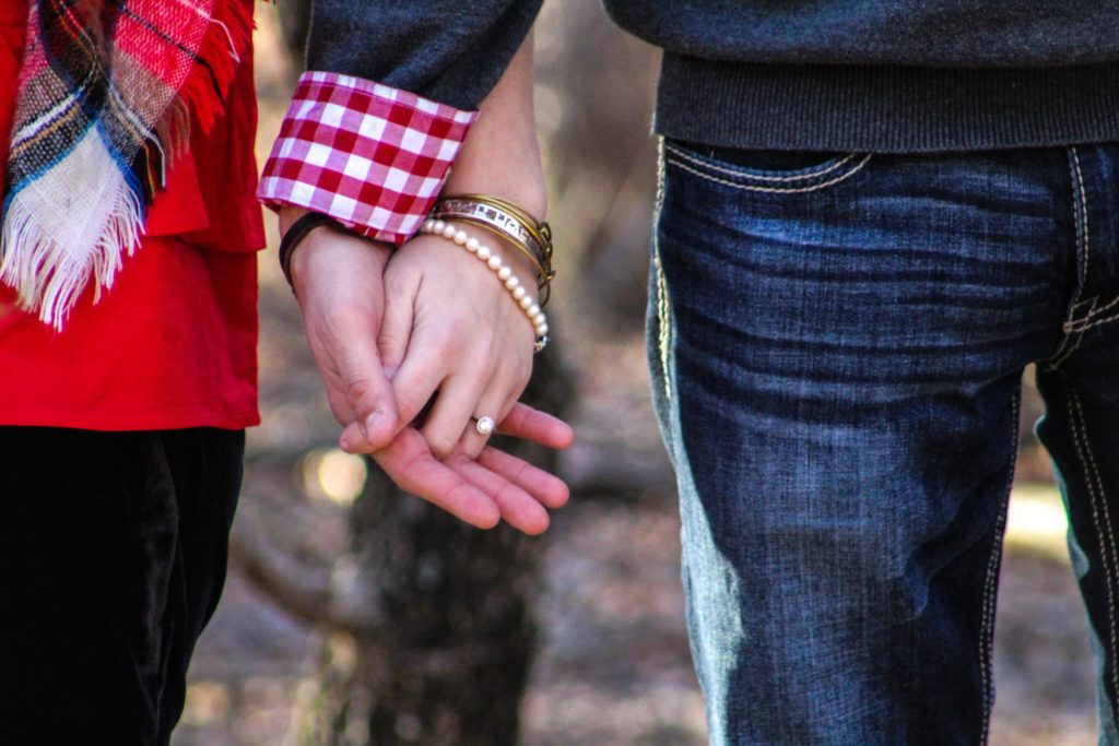 two people holding hands | How to Pick the Perfect Fall Engagement Photos Outfit