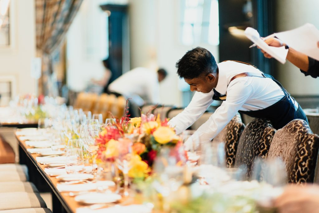 caterers set up the dinner table | Should I Hire a Day-of Wedding Coordinator?