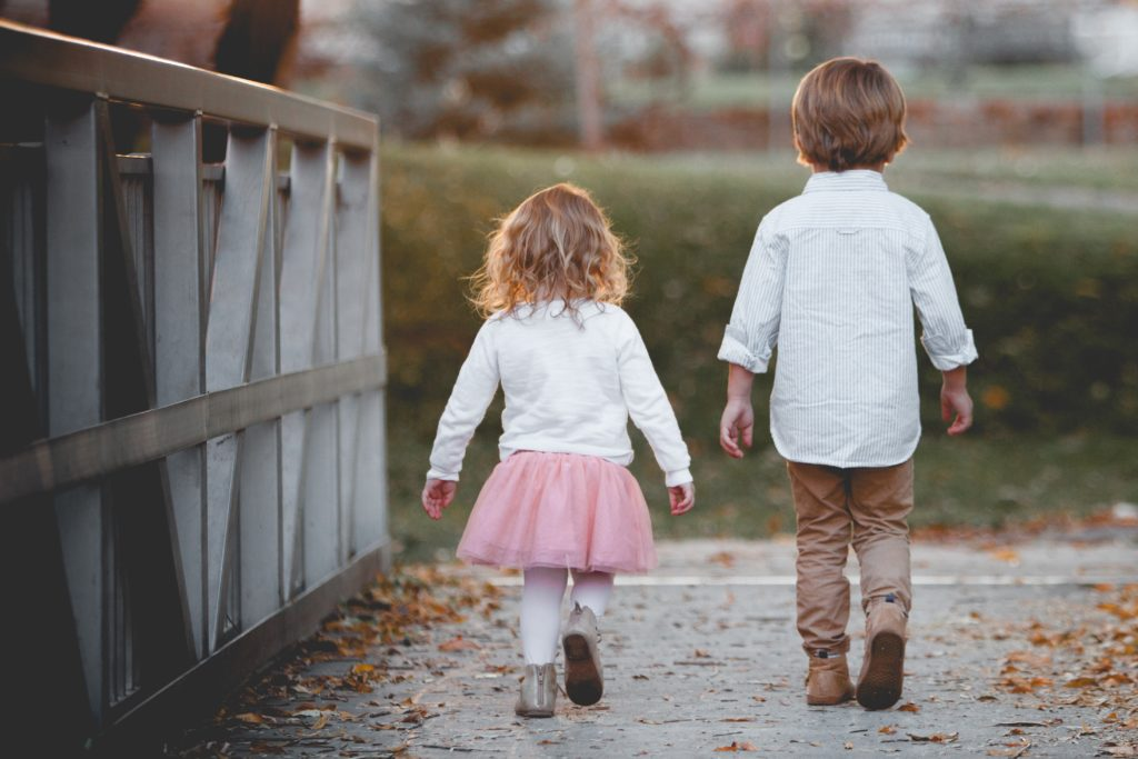 two kids walking together on a bridge | Should I Have Kids at My Wedding?