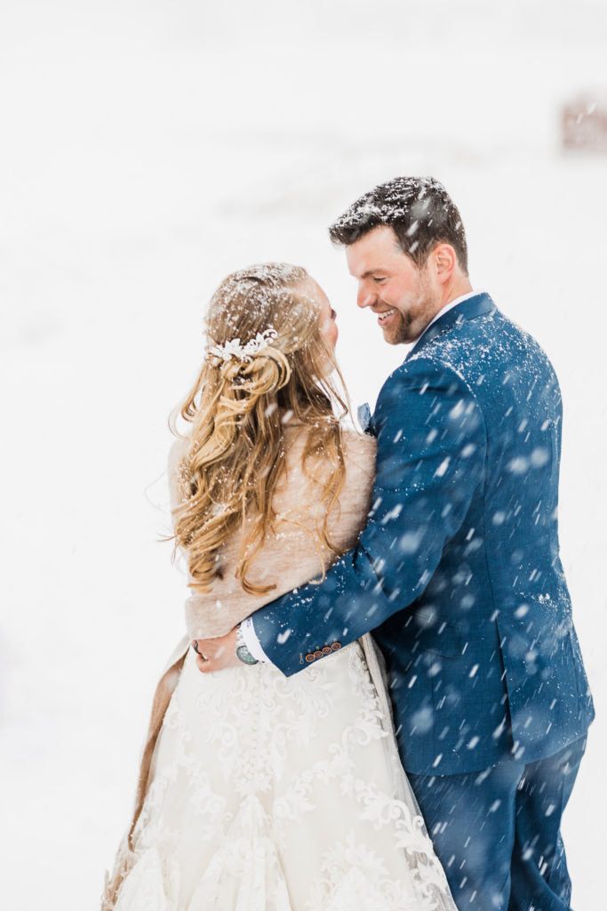 couple smiling at each other in the snow | What to Wear to a Winter Wedding