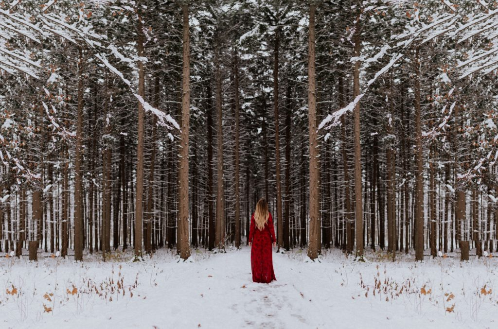 girl standing in the forest | What to Wear to a Winter Wedding