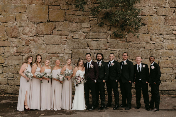 Bridal Party lined up in front of a beautiful stone wall. Groomsmen are wearing black suits.
