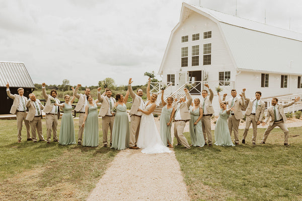Bridal Party excitedly cheering in front of white barn and countryside setting.