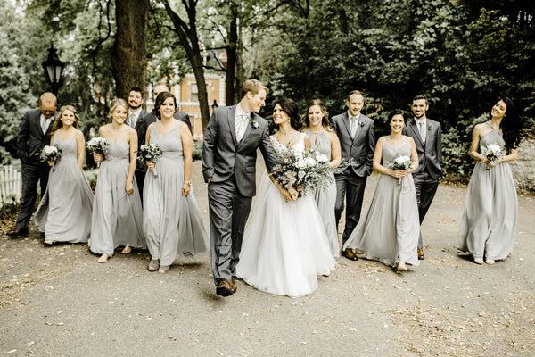 Bridal Party strolling down a tree covered sidewalk. Groomsmen are wearing grey suits and ties.