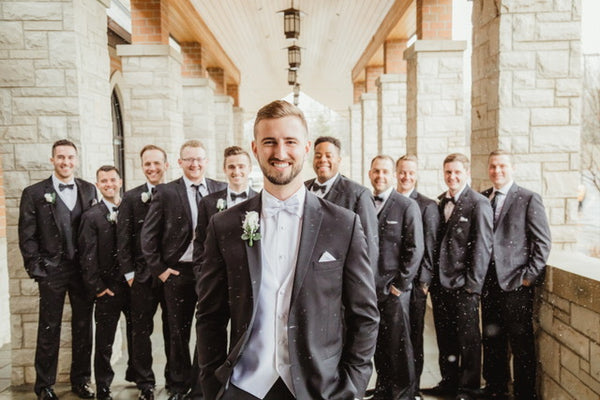 Groom in tuxedo, white vest, and white bowtie. Groomsmen wearing tuxedos and black bowties.