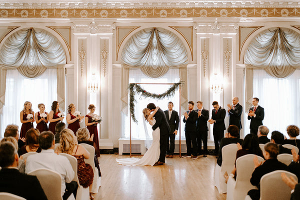 Bride and Groom underneath a decorated pergola in a grand ballroom during their ceremony.