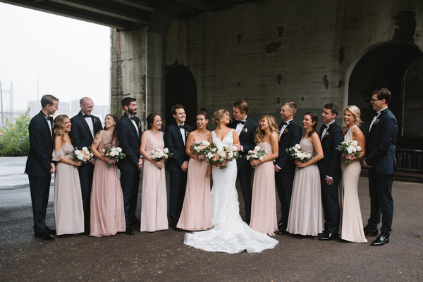 Bridal Party lined up in front of an industrial background. Groomsmen are wearing tuxedos and bowties.