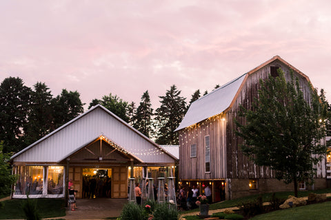 Refurbished barn and building set up for a wedding reception. Twinkly lights drape across the side.