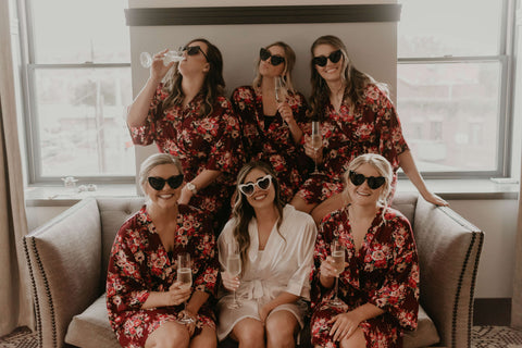 Bride and Bridesmaids wearing matching robes and heart-shaped sunglasses, holding glasses of champagne.