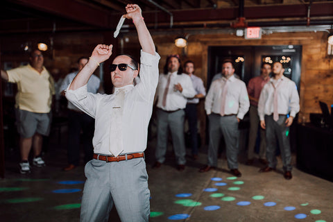 Groom wearing sunglasses, getting ready to throw the garter to a crowd of guys