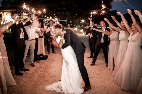 Bride and Groom dipping for a kiss, surrounded by two rows of guests holding sparklers.