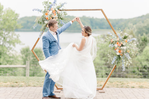 Bride and Groom twirling beneath a floral decorated pergola.