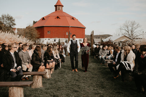 Ceremony is set outside in a woodsy area. The pews are made of wood and have tree stumps as support. Bridesmaid and Groomsman walking down the aisle.