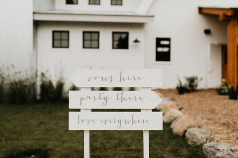 """Wooden sign with various arrows, stating: """" Vow Here"""", """"Party There"""", """"Love Everywhere"""""""