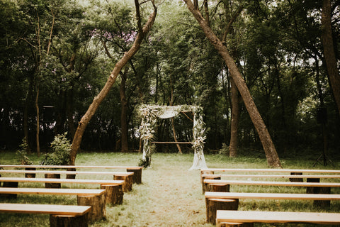 Ceremony is set up in a wooden area with simple wooden pews and a decorated pergola