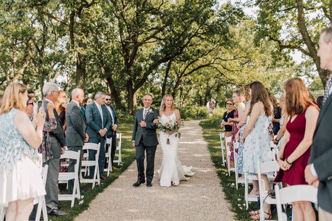 Bride and her father walking down the aisle. The ceremony is set up outside with beautiful greenery surrounding.