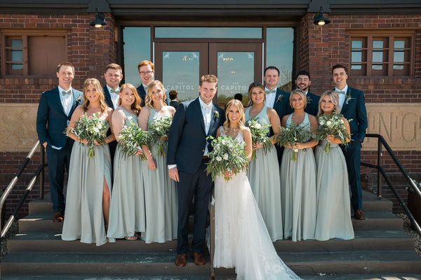 Bridal Party posing together on stairs in front of brick building. Bride is wearing 'Rebecca Ingram Raelynn' Dress from the Wedding Shoppe.