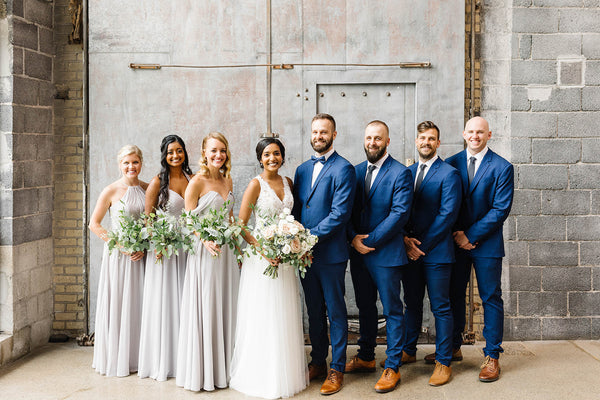 Bridal Party in front of a stone brick building. Groomsmen are wearing blue suits and brown dress shoes.