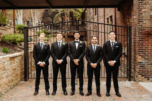 Groomsmen in black tuxedos lined up on a brick pathway outside of a brick building.