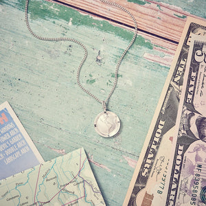 Unusual travel gifts for a man, silver globe necklace