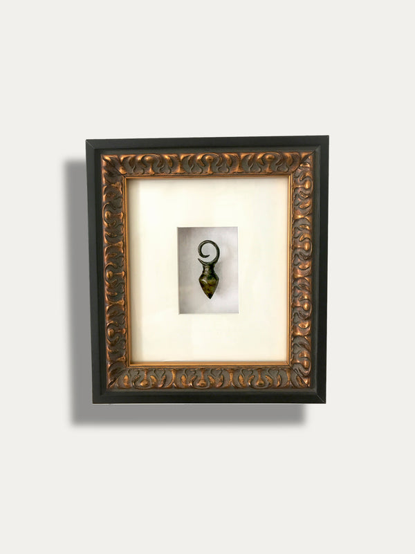 A STRIKING BRASS EAR WEIGHT FROM BORN ENCAPSULATED INSIDE A WOODEN FRAME, A SYMBOL OF GREAT ACHIEVEMENT