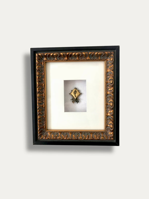 FRAME WITH MAMULI EARRING FROM SUMBA INCAPSULATED INSIDE A WOODEN FRAME, A SYMBOL OF FERTILITY