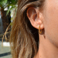 de rayos de sol y confeccionados en plata de ley con baño de oro 18 kilates. Gold plated sterling silver medium hoop earrings with shape of a sun