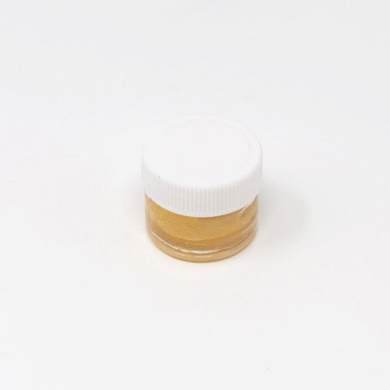 Honey colored CBD extract in small clear container with closed white lid.