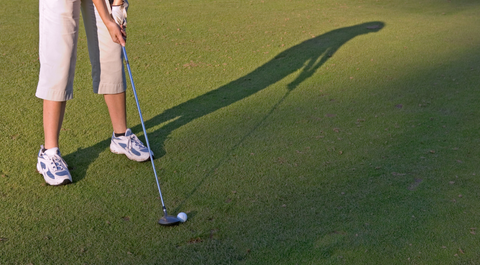 woman on golf course putting