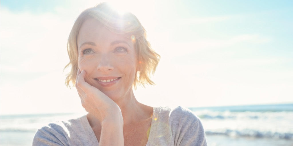 smiling woman at beach with sunlight