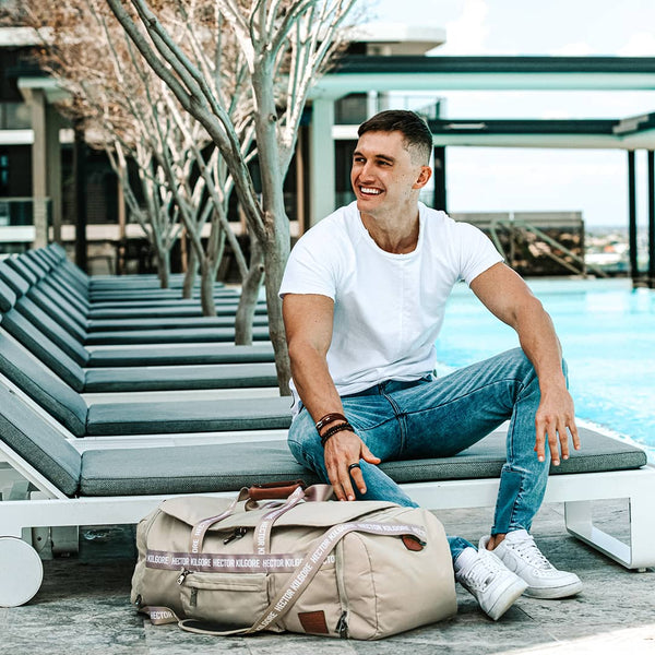Man sitting by the pool with cream beige duffle travel bag