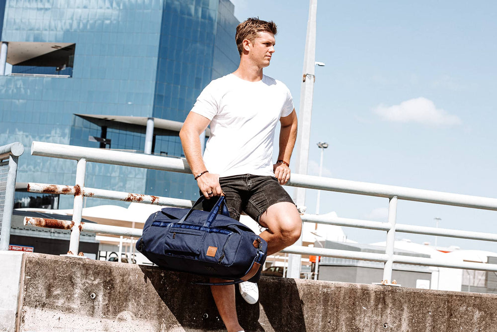 Man standing with navy travel bag in cityscape